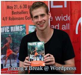"""Rafe Bartholomew poses with a paperback edition of Pacific Rims"""